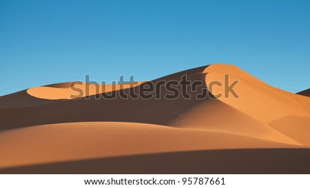 Sand dunes with clear blue sky, Chigaga Desert, Moroccan Sahara - stock photo