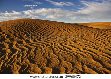 sand dunes with cloudy blue sky in the Sahara desert - stock photo