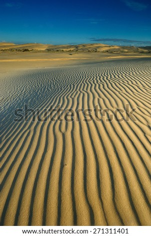 Sand dunes with sand patterns and lines and a shadow below the dune - stock photo