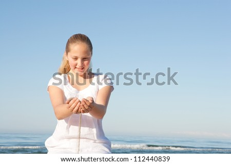 Sand filtering through a young girl's hands while sitting down on a beach with the sea in the background, smiling.