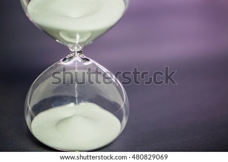 Sand flowing through an hourglass on dark background concept for time running out.