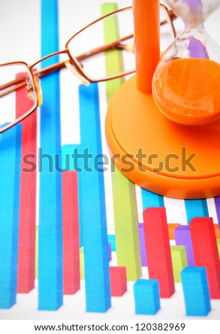 Sand-glass and glasses on graphs. - stock photo