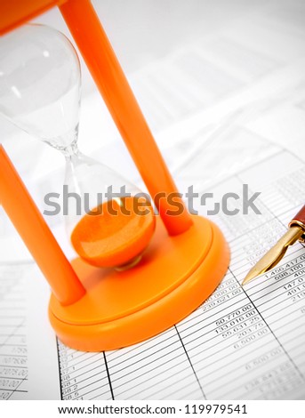 Sand-glass and pen on documents. - stock photo