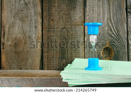 Sand-glass and writing-books. On a wooden background. - stock photo