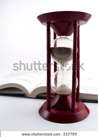 sand glass, open book in the background - stock photo