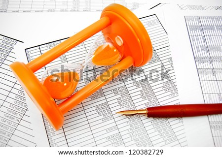 Sand-glass, pen on documents. - stock photo