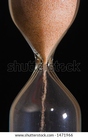 Sand-glass with flowing sand took close - stock photo