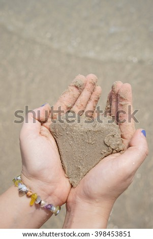 sand heart shaping female hands above beach