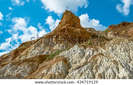 Sand hill against the blue sky with clouds. - stock photo