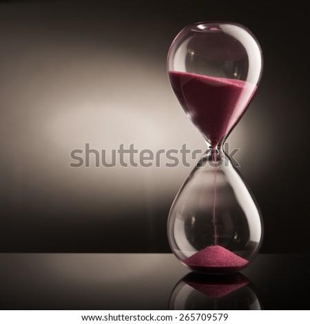 Sand hourglass on glass table - stock photo
