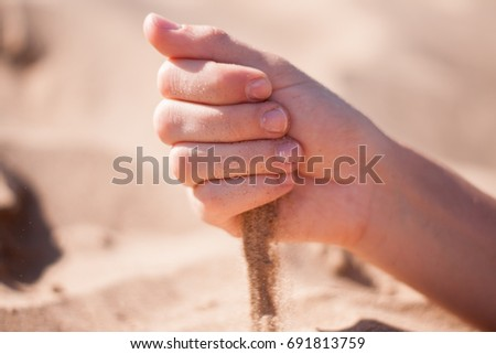 Sand is poured from the hand