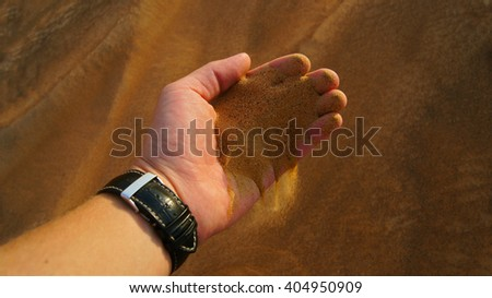 Sand, man's hand and a watch