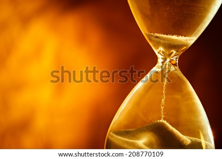 Sand passing through the glass bulbs of an hourglass measuring the passing time as it counts down to a deadline or closure on a yellow background with copyspace - stock photo
