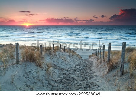 sand path to North sea beach before sunset, Holland - stock photo