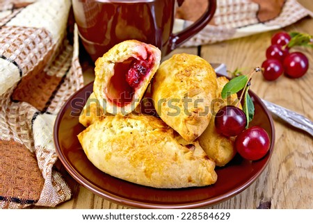 Sand pies with cherries on a plate, cup, napkin on a wooden boards background - stock photo