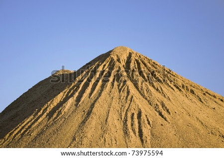 Sand pile with blue sky - stock photo