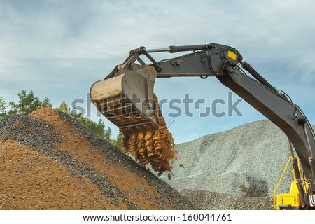 sand pouring from scoop of excavator - stock photo