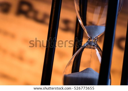 Sand running through an hourglass measuring passing time counting down towards a deadline, close up view of the glass bulbs with a blurred written document behind and copy space