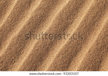 Sand shaped into parallel ridges by the wind. - stock photo