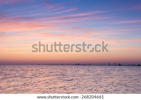 Sand spit in the blue sea and people silhouettes on a background picturesque purple sunset in the summer evening - stock photo