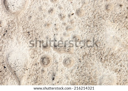 Sand surface after the rain with the visible traces of the raindrops - stock photo