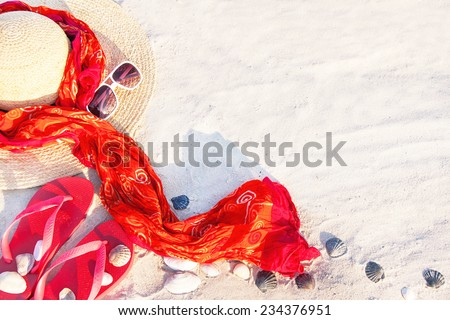 Sand texture (background) with flip flop sandals, hat, pareos (sarong), sunglasses, shellfishes (scallop) on the beach. The empty pattern for message. Summer vacations (travel) concept. Copy space.  - stock photo