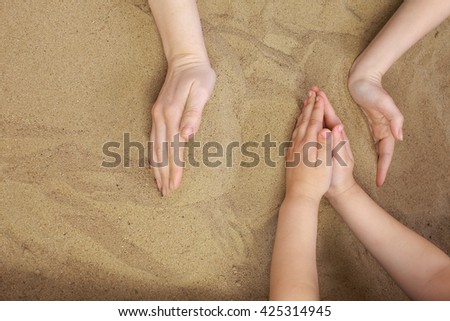 sand therapy.Hands adult and child playing in the sand