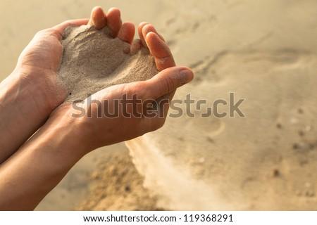 Sand through his fingers - stock photo