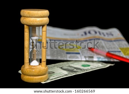 sand timer with dollar bill and classified sections in newspaper