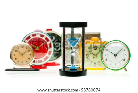 Sand timer with vintage mechanical wind-up alarm clocks on white background, shallow focus - stock photo