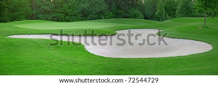 sand trap on the green grass of the golf course - stock photo