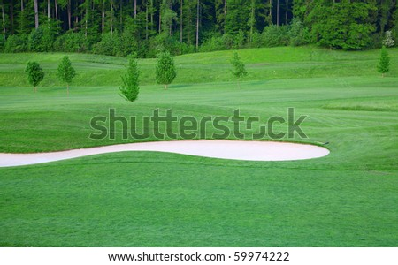 Sand trap on the green grass of the golf field - stock photo