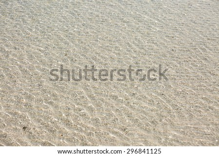 Sand under sea water against sunlight - stock photo