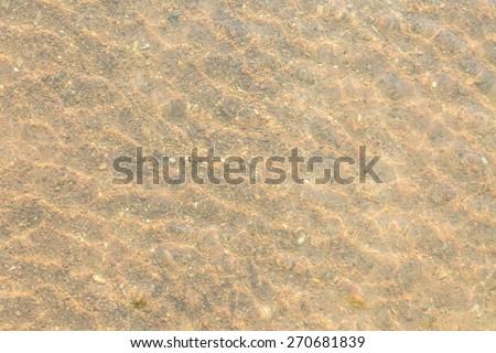 Sand under sea water against sunshine - stock photo