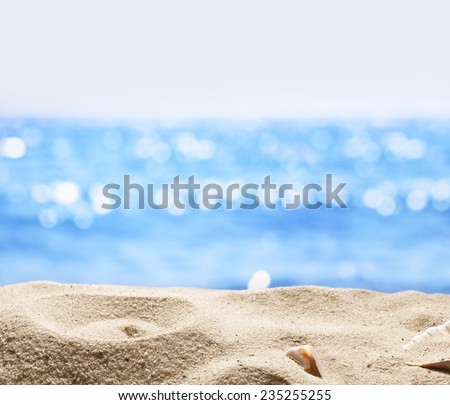 Sand with blurred sea background. File has clipping path for holes in the sand. You can insert the bottle or glass. - stock photo