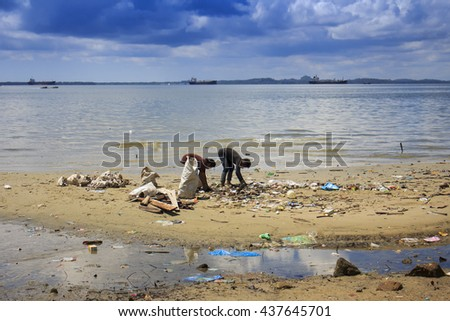 SANDAKAN, MALAYSIA - 16 JUNE 2016: Beach cleanup: refuse collection on polluted beach with plastic pollution - stock photo