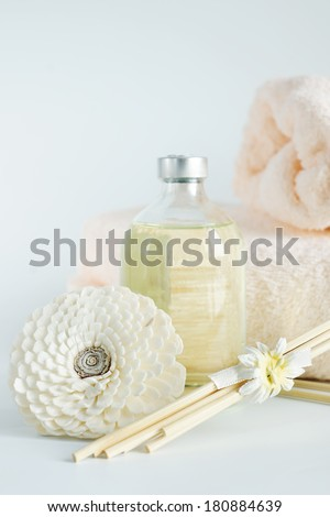 Sandal oil in a bottle and towels for spa procedures - stock photo