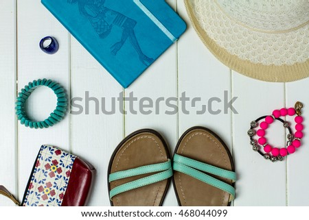 Sandals and accessories, set out for a walk on a white wooden background