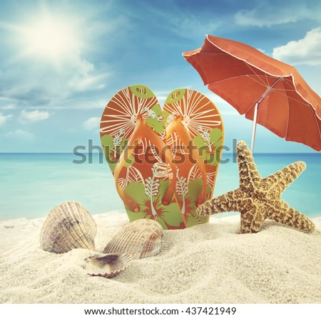 Sandals and starfish with beach umbrella at the ocean - stock photo