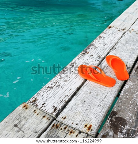 Sandals at jetty by the sea - stock photo