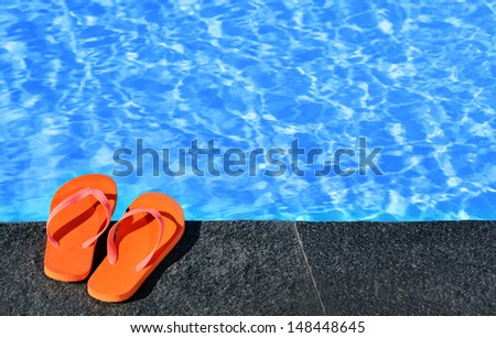 sandals by a pool - stock photo