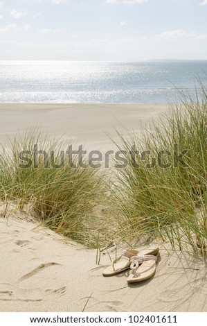 sandals in sand dunes with beach and sea in background - stock photo
