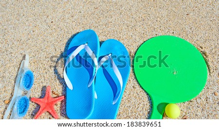 sandals, rackets and sea goggles on a golden shore