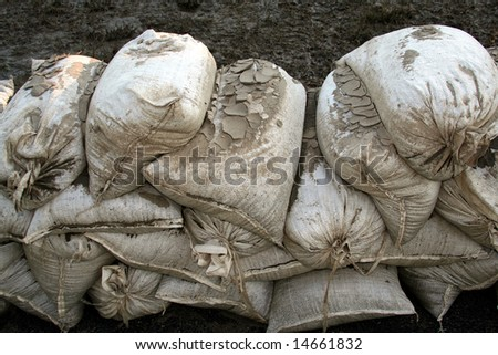 Sandbags are caked  with dried mud as the flood waters recede. - stock photo