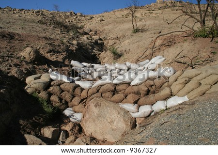 sandbags to prevent erosion of a burnt out hill - stock photo