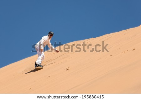Sandboarder going down the slope - stock photo