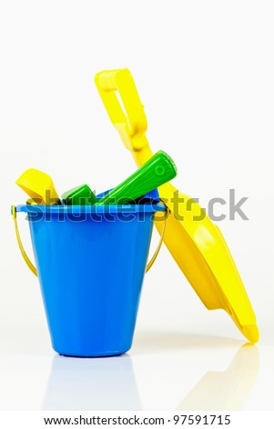 Sandbox Toys including a blue kids bucket and a yellow kids shovel.