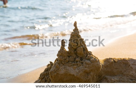 Sandcastle against of sunlight reflection, Sandy beach of Corfu, Greece.
