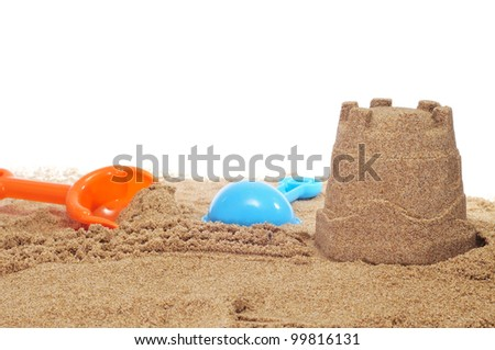 sandcastle and beach shovels on a white background - stock photo