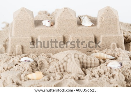 Sandcastle and sea shells on white background